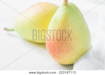 Couple of Ripe Organic Pears in Pastel Green Yellow Red Colors on White Wood and Linen Fabric. Elegant Minimalist Japanese Style. Creative Image for Social Media Blog Product Branding. Healthy Food