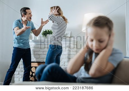 Unhappy family. Unsmiling fair-haired little girl closing her ears and sitting on the sofa while her parents shouting at each other