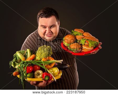 Diet fat man who makes choice between healthy and unhealthy food . Overweight male with hamburgers and vegetables. How to make stock of products in case of war.