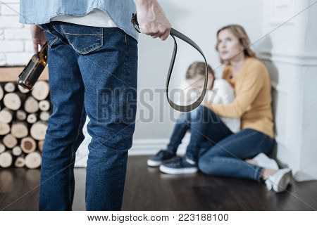 Fear. Terrified miserable fair-haired mother and girl sitting in the corner while daddy standing in front of them and holding a belt and a bottle