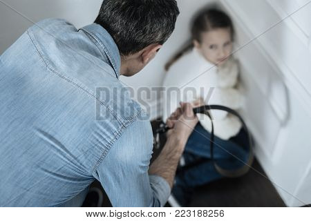 Aggression. Scared miserable fair-haired girl sitting in the corner while daddy holding a belt and beating her
