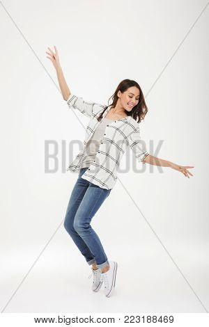 Full length image of Cheerful brunette woman in shirt dancing over gray background