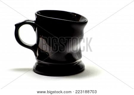 studio photography of a dented black porcelain cup isolated on white