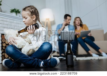 Beer. Miserable fair-haired little girl holding a bottle of beer and giving it to her teddy bear while her parents working on their laptops