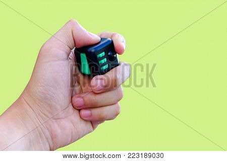 Fidget Cube stress reliever, fingers toy in bokeh background, black. (relax)