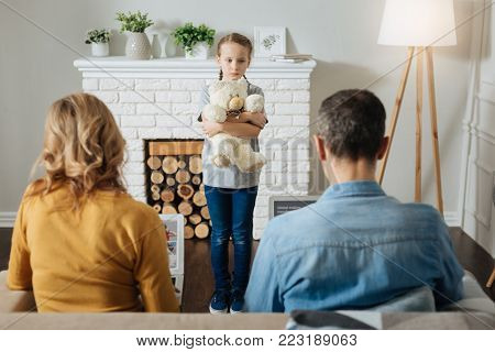 Lonely. Lonely blond little girl holding her teddy bear and standing in front of her parents while they working on their laptops