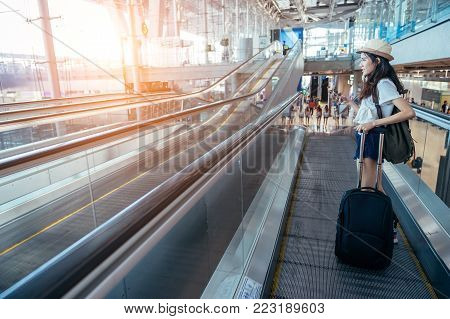 Asian teenage girl is using a smartphone to check flight at the international airport to travel on weekends.