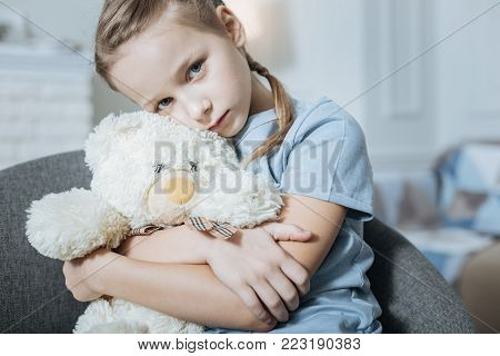 My bear. Miserable fair-haired blue-eyed little girl hugging and holding her teddy bear while sitting in the armchair