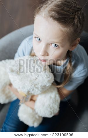 Being alone. Unsmiling blue-eyed little girl hugging and holding her teddy bear while sitting in the armchair