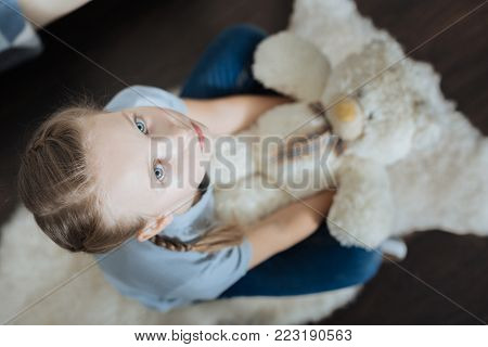 I am lonely. Miserable blue-eyed little girl hugging and holding her teddy bear while sitting in the armchair