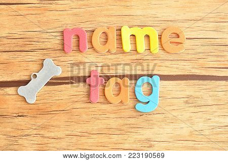 A bone shape name tag for a dog with the word name tag