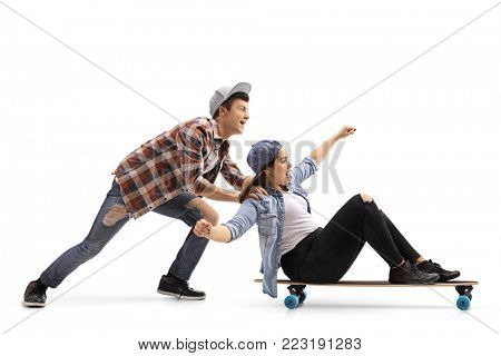 Teenage boy pushing a teenage girl on a longboard isolated on white background