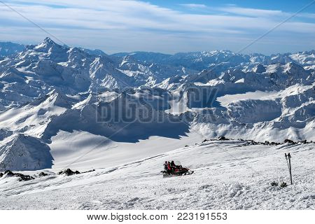 Tourists on the snowmobile quickly rise to the top on the background of beautiful scenery in the mountains of Elbrus