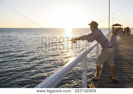young attractive and happy man in shirt and hat fishing at beach sea dock using fish road enjoying weekend hobby in holidays and relaxing tourism concept on sunset