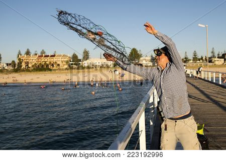 young happy and proud attractive fisherman throwing fish and crabs basket net at sea dock sunset in man fishing as weekend hobby concept and holidays leisure concept