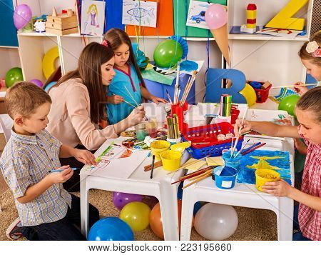 Kids playroom organization of children painting and drawing kid's club. Craft lesson in primary school. Kindergarten teacher and students work together. Creation of creative environment for children.