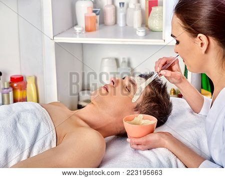 Mud facial mask of man in spa salon. Massage with mud from full face. Male lying spa bed. Beautician with bowl therapeutic procedure . Anti-aging cosmetic dead sea mud mask.