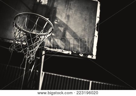 Closeup view of basketball hoop by night.