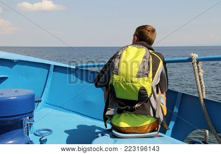 a man sits on the edge of the boat. boat floats on the water. the guy riding on the boat.