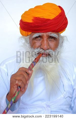 JODHPUR, RAJASTHAN, INDIA - DECEMBER 17, 2017: Portrait of a man with long white mustache (whiskers) and beard and an orange turban in  Mehrangarh fort