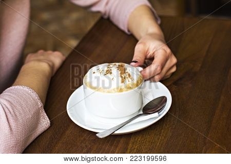 Female Hands Hold A Cup Of Cappuccino In A Cafe.