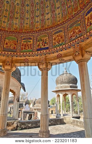 DUNDLOD, RAJASTHAN, INDIA - DECEMBER 27, 2017: General view of a well with turrets and cenotaphs and mural paintings in the foreground