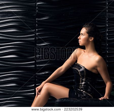Young beautiful woman in short black dress posing on the couch. Portrait in profile. Black wavy wall in the background