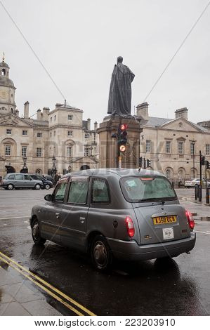A Licensed London Taxi stopped at a red light traffic signal opposite Horse Guards Parade on a dreary wet day.  The area is popular with tourists visiting the capital especially on a wet rainy day, London, England, 2018