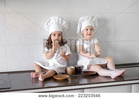 two little baker girls are drinking tea with a pabcakes in the kitchen. poster