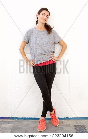 Confident Young Woman In Sportswear Standing By A White Wall