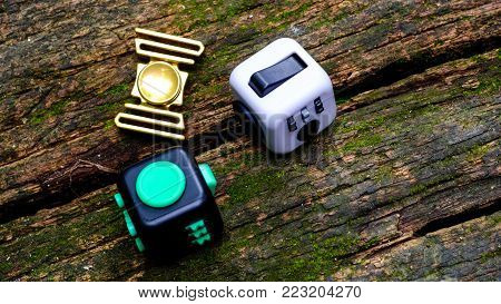 Fidget Cube stress reliever, fingers toy on old wooden floors background, spinner(relax)