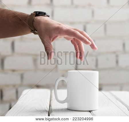 Man's hand is going to take a blank white cup from table. Closeup shot