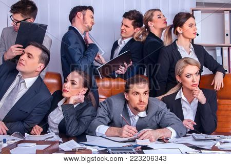 Business people office life of team people are happy with hand up sitting table and working papers . Lazy employees in team. Lack of motivation at work.