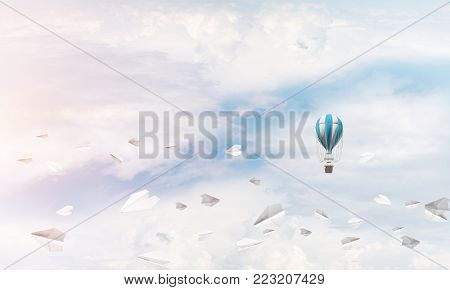 Colorful aerostat flying among paper planes and over the blue cloudy sky.