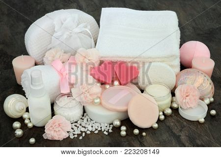 Luxury spa beauty treatment with pink heart shaped soaps, ex foliating scrub, face cloths, moisturising cream, body lotion, powder puffs, carnation flowers with seashells and pearls.