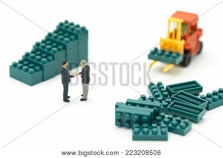 Miniature 2 people businessmen Shake hands with High-lifted forklift trucks are a great way to grow your business as a high-tech, high-growth joint venture.business concept with  copy spaces for your