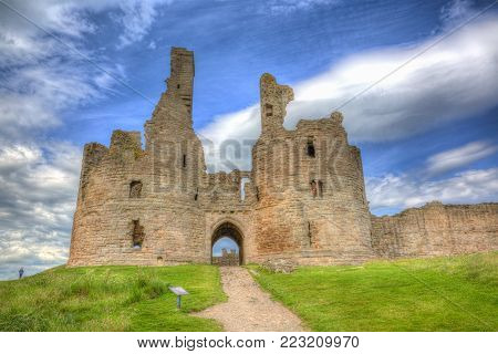 English medieval castle Dunstanburgh Northumberland England uk in colourful hdr