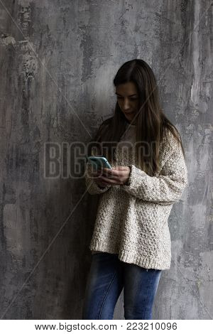 Young Woman In A Beige Cardigan Stands Against The Gray Wall And Talks On The Phone