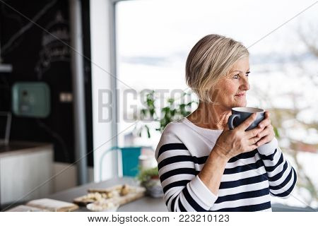 Senior woman in the kitchen. An old woman inside the house, holding a cup of coffee.