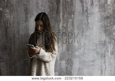 A Young Woman In A Beige Cardigan Looking In The Phone