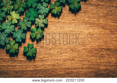 Green wooden four leaf shamrocks laying on a wooden board. St. Patrick's day. Irish culture.