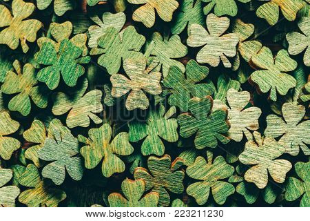 Pile of wooden green four-leaf clovers laying down. Luck symbol. St. Patrick's day.