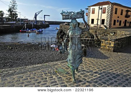 PUERTO DE LA CRUZ, SPAIN - JUNE 15: A sculpture of a fishwife in the fishing port on June 15, 2011 in Puerto de la Cruz, Spain. This statue, from Julio Nieto, pays homage to the ancient fish vendors