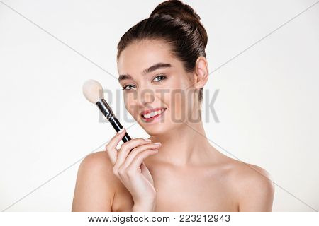 Bright photo of smiling half-naked woman with fresh skin holding brush for makeup close to face, applying concealer isolated over white wall