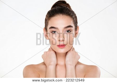 Horizontal portrait of beautiful young woman with fresh skin touching her neck, posing over white background with meaningful look