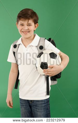 Happy little schoolboy with backpack and football.