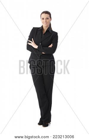 Confident businesswoman standing with arms crossed, smiling at camera, full size portrait isolated on white.
