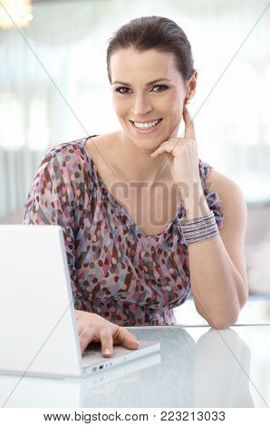 Cheerful attractive office worker mid-adult woman, using laptop computer, smiling at camera.