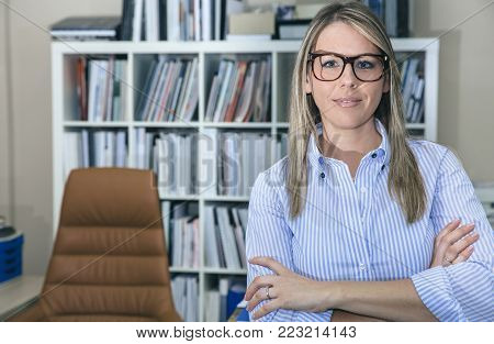 Portrait of young smiling businesswoman standing in office against of bookcase