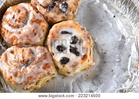 Closeup of a tin of homemade cinnamon buns. Four buns some with raising others without. Half the tray is empty.